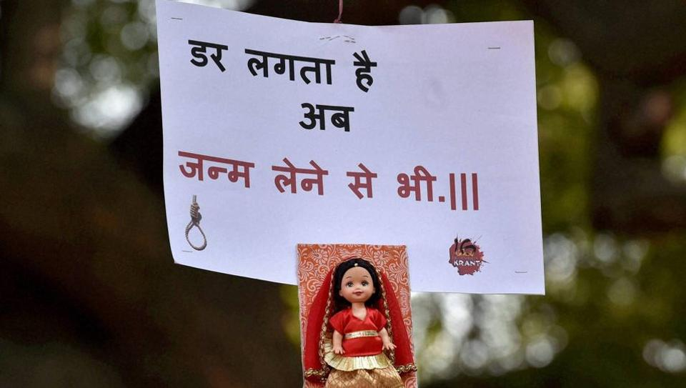 A placard with a doll hangs from the branch of a tree during a programme to mark the third anniversary of Nirbhaya gang-rape case at Jantar Mantar in New Delhi on Wednesday. PTI Photo by Kamal Singh (PTI12_16_2015_000233B)