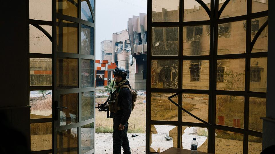 A member of the Iraqi special forces' Counter-Terrorism Service (CTS) stands guard next to a damaged building at Mosul's university on January 15, 2017, during an ongoing military operation against Islamic State (IS) group jihadists.