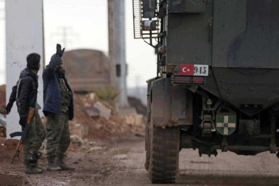 Free Syrian Army fighters gesture as Turkish military vehicles drive in the Syrian rebel-held town of al-Rai while heading towards the northern Syrian town of al-Bab.