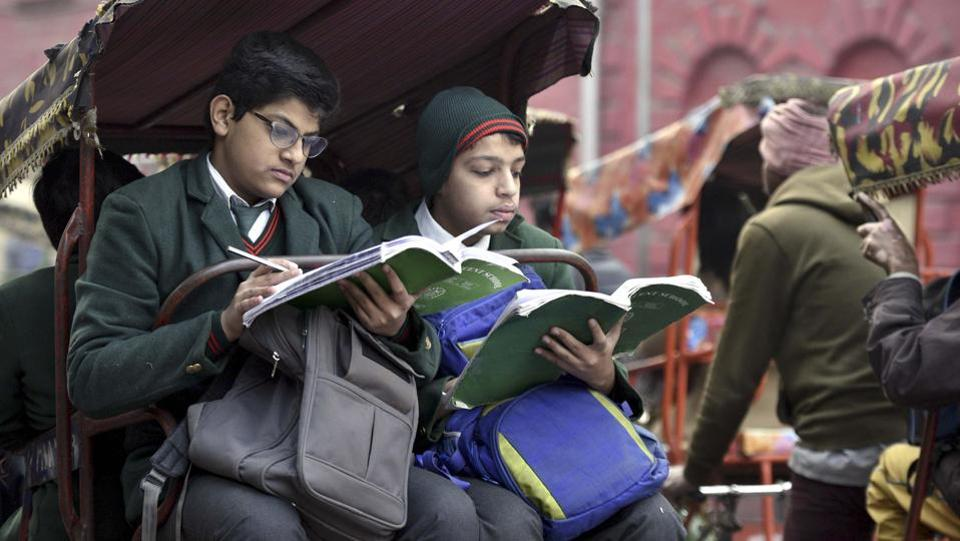 Schoolchildren engrossed in studies as they ride on the back of  a cycle-rickshaw to school. (Arun Sharma/HT PHOTO)