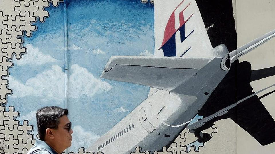 This file picture taken on March 8, 2016 shows a man walking in front of a mural of missing Malaysia Airlines MH370 plane in a back-alley in Shah Alam, Malaysia.