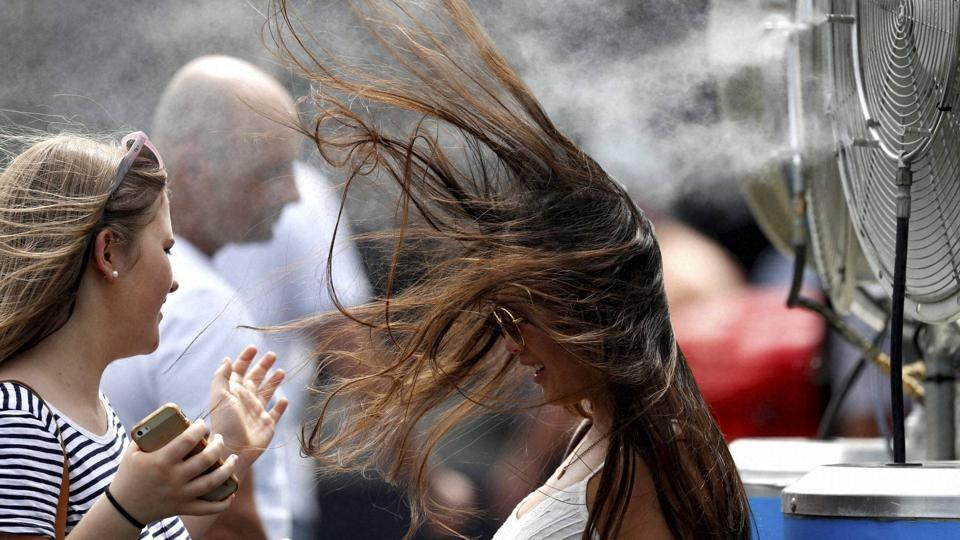 Hair-raising tennis may not have been the order of the day in the first-round matches at the Australian Open on Tuesday. But fans found some moments of their own at the water spraying fan. (AP)