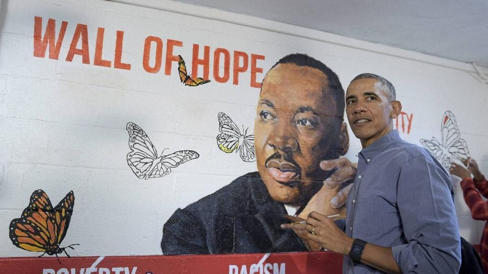 President Barack Obama helps paint a mural of Martin Luther King Jr. in Washington on Monday.