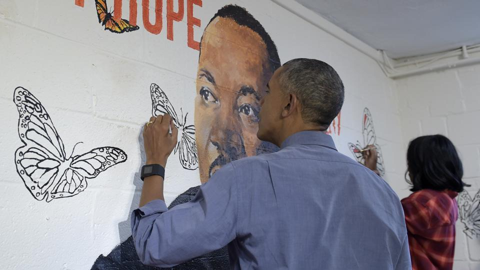 President Barack Obama and first lady Michelle Obama help paint a mural of Martin Luther King, Jr., in the community room of the Jobs Have Priority Naylor Road Family Shelter in Washington. The mural,