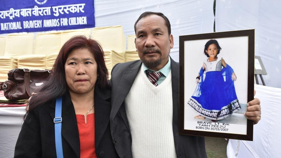 Tarh Peeju's parents hold a picture of their daughter who won an award (Posthumously) for saving two children from drowning in a river, losing her life because of strong undercurrents. (Mohd Zakir/HT Photo)