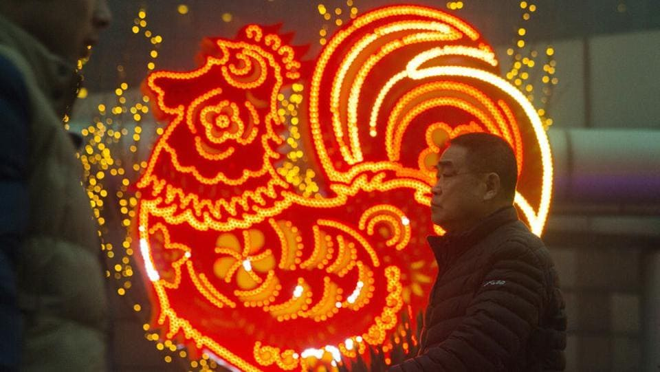 Chinese men walk past neon decorations marking the Year of the Rooster in Beijing on Monday.  (Ng Han Guan) / AP)