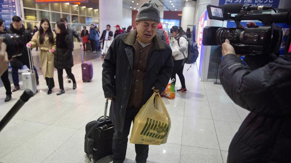Wen Wanchang, whose son was on board the missing Malaysia Airlines Flight 370, reacts to journalists filming him as he arrives at the train station in Beijing, China, January 17, 2017. Some relatives of Flight 370's passengers expressed anger, disappointment and a resolve to press authorities to resume their efforts and find out exactly what happened. Others said they understood that the search — the most expensive of its kind in aviation history — had to come to an end.   (AP)