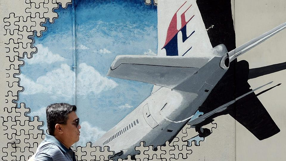 This file picture taken on March 8, 2016 shows a man walking in front of a mural of missing Malaysia Airlines MH370 plane in a back-alley in Shah Alam, Malaysia. The deep ocean hunt for MH370 has been suspended after nearly three years without result, the Australian, Malaysian and Chinese governments have said.  (AFP)