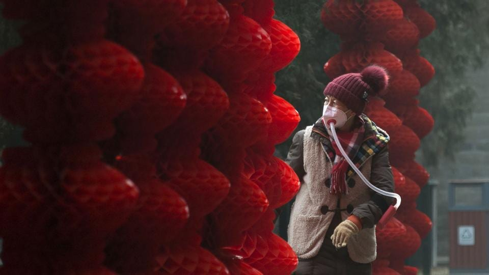 An elderly woman wearing a home-made mask walks past lanterns hung ahead of the Lunar New Year at a park in Beijing on Tuesday.  (WANG Zhao / AFP)