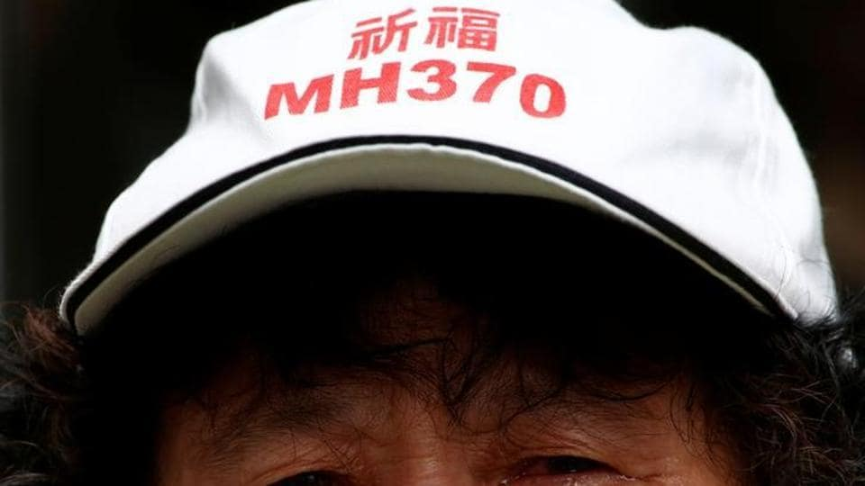 A family member of a passenger aboard Malaysia Airlines flight MH370, which went missing in 2014, reacts during a protest outside the Chinese foreign ministry in Beijing on July 29, 2016. The hat reads