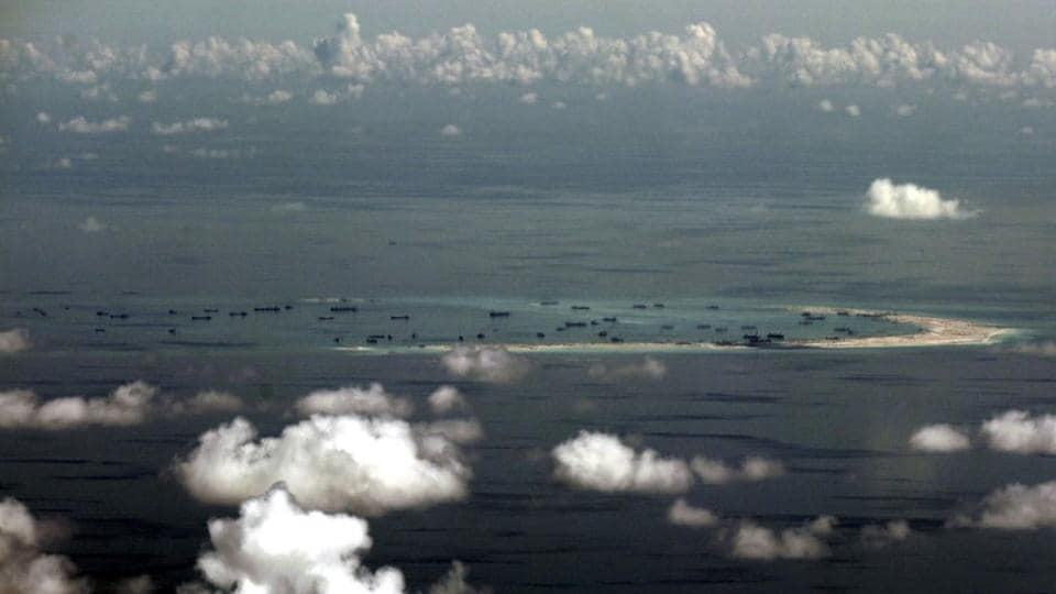 An aerial photo taken though a glass window of a Philippine military plane shows alleged ongoing land reclamation by China on Mischief Reef in the Spratly Islands in the South China Sea in May 2015.
