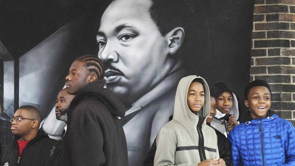 Students and MLK Legacy March participants wait near a huge wall hanging of Dr. Martin Luther King Jr. before the start of the 8th annual MLK Legacy march in honour of the Martin Luther King Jr. holiday in Detroit. (Daniel Mears/Detroit News via AP)