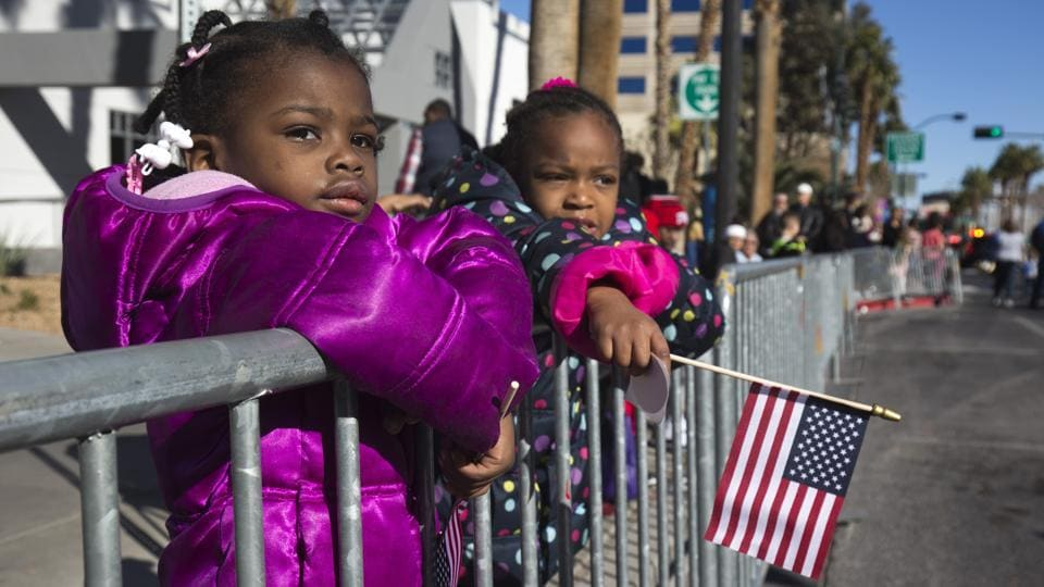 Ivey Holley, 2, and Alisha Miniweather, 5, watch the Martin Luther King Jr. Day parade in downtown Las Vegas. (Steve Marcus/ Las Vegas Sun via AP)