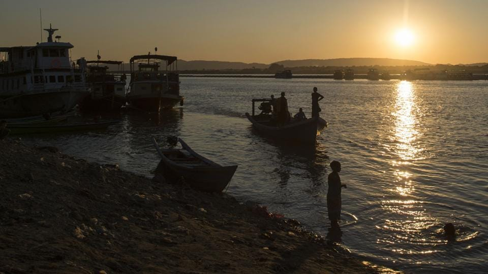 This photo taken on November 23, 2016 shows people using boats to travel over the Irrawaddy river near Mandalay. For Irrawaddy locals, losing the dolphins is not just about destroying traditions from their past -- it threatens their future. With fish stocks plummeting there are hopes ecotourism will prove a lifeline to bolster meagre incomes. (Ye Aung Thu/AFP)