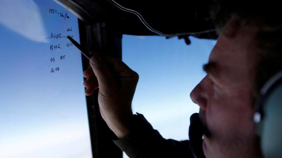 Squadron leader Brett McKenzie marks the name of another search aircraft on the windshield of a Royal New Zealand Air Force P-3K2 Orion aircraft searching for missing MH370 over the southern Indian Ocean on March 22, 2014.   (REUTERS)