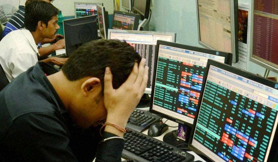 In this file photo share brokers are seen reacting to falling stock prices on screens of computers and television.