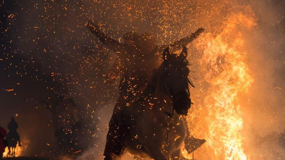 A horseman jumps over a bonfire...all fire and heat.  (AFP)