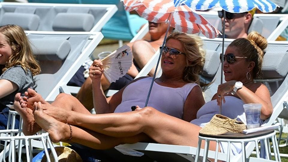 Fans catching some hot Australian Open tennis action under the umbrella.  (AFP/Getty Images)