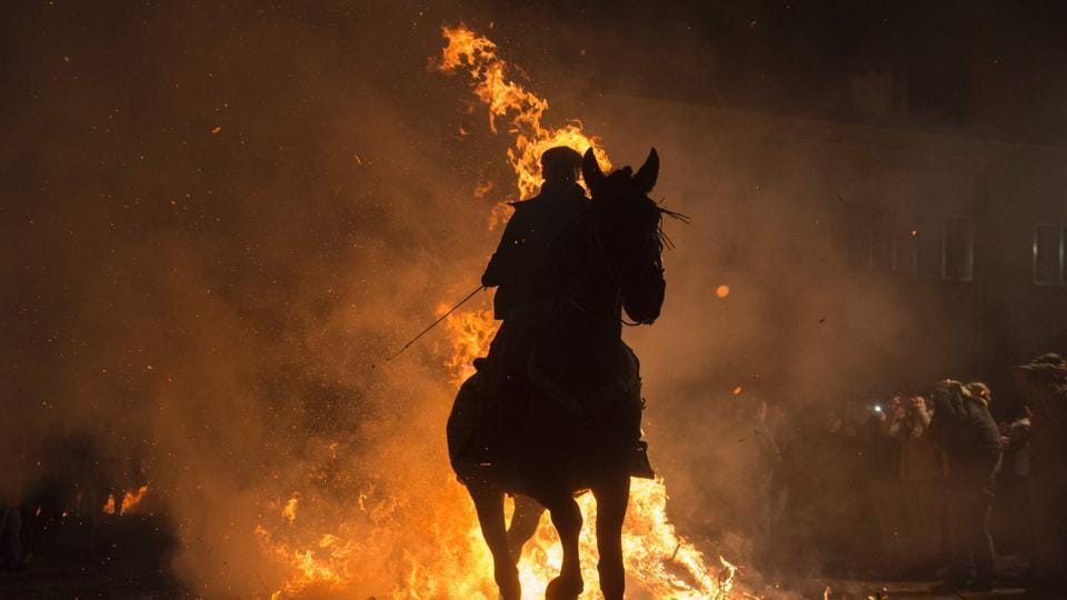 A horseman jumps over a bonfire in the village of San Bartolome de Pinares in the province of Avila, Castile and Leon in central Spain, during the opening of the traditional religious festival Luminarias on January 16, 2017.  (AFP)