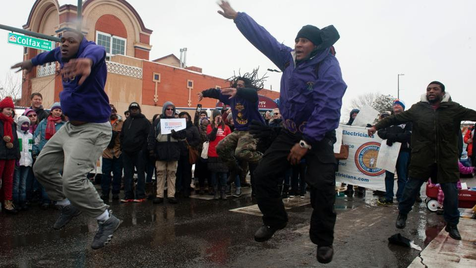 Omega Psi Phi Fraternity members perform 'We Jump' while marching down Colfax Avenue in Denver, Colorado during Denver's Martin Luther King Jr. parade. Denver's Martin Luther King Jr. parade is the largest celebration held in honour of the late Dr. Martin Luther King Jr. in the United States.  (Jason Connolly/AFP)