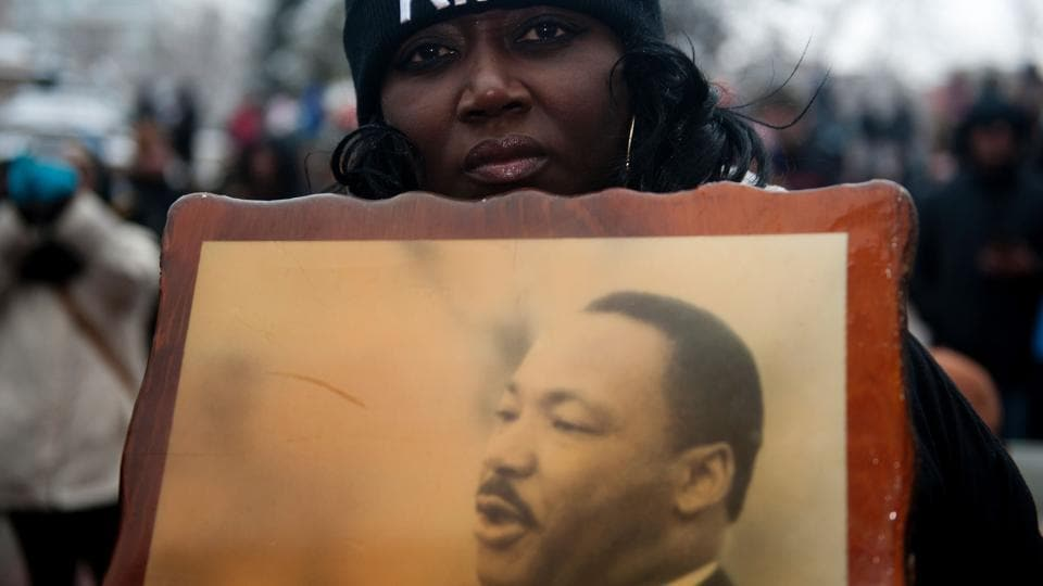 Bridget Johnson holds a picture of the late Dr. Martin Luther King Jr. while marching in Denver, Colorado during Denver's Martin Luther King Jr. parade. (Jason Connolly/AFP)