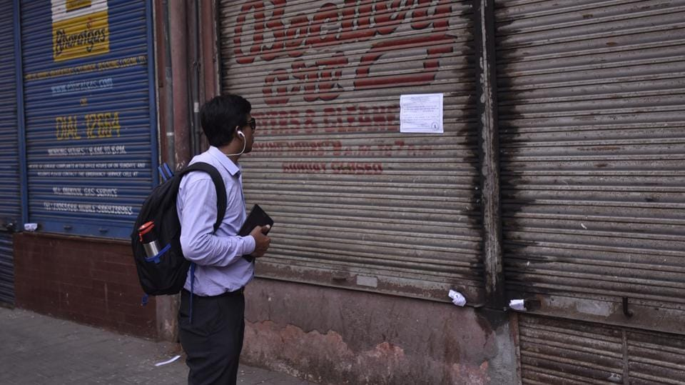 A passerby reads the collector's notice on building that houses Eros Cinema on Wednesday. Shows at the theater, too, have been abruptly stopped. (kunal patil/ht photo)