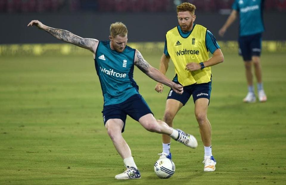 England's Jonny Bairstow (R) and Ben Stokes kick a ball during a training session at the Barabati stadium. (AFP)