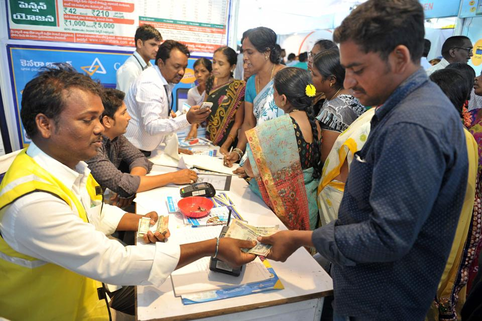 An Indian visitor (R) receives cash from a bank employee after withdrawing money from his bank account with his Aadhaar or Unique Identification (UID) card during a Digi Dhan Mela, held to promote digital payment, in Hyderabad.