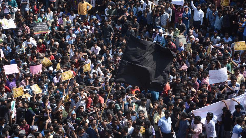 Protesters wave black flags as the support for Jallikattu gathered momentum after a major rally at Marina Beach at Chennai on Wednesday.  (AFP)
