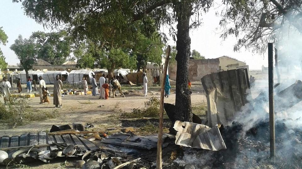 This hand-out image received in courtesy of Doctors Without Border (MSF) on January 17, 2017, shows people standing next to the destruction after an air force jet accidentally bombarded a camp for those displaced by Boko Haram Islamists, in Rann, northeast Nigeria. At least 100 aid workers and civilians were killed.