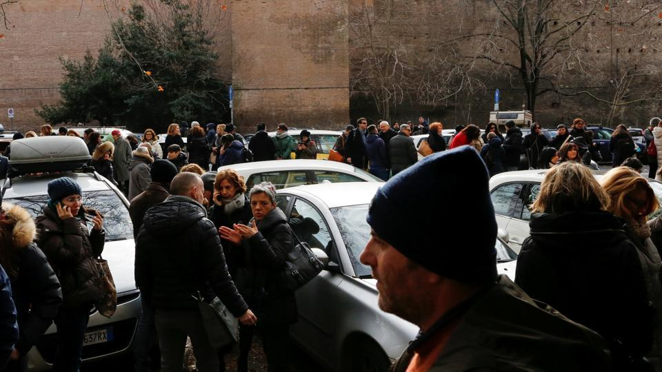 People stand on the road after leaving buildings following an earthquake in Rome on Wednesday.