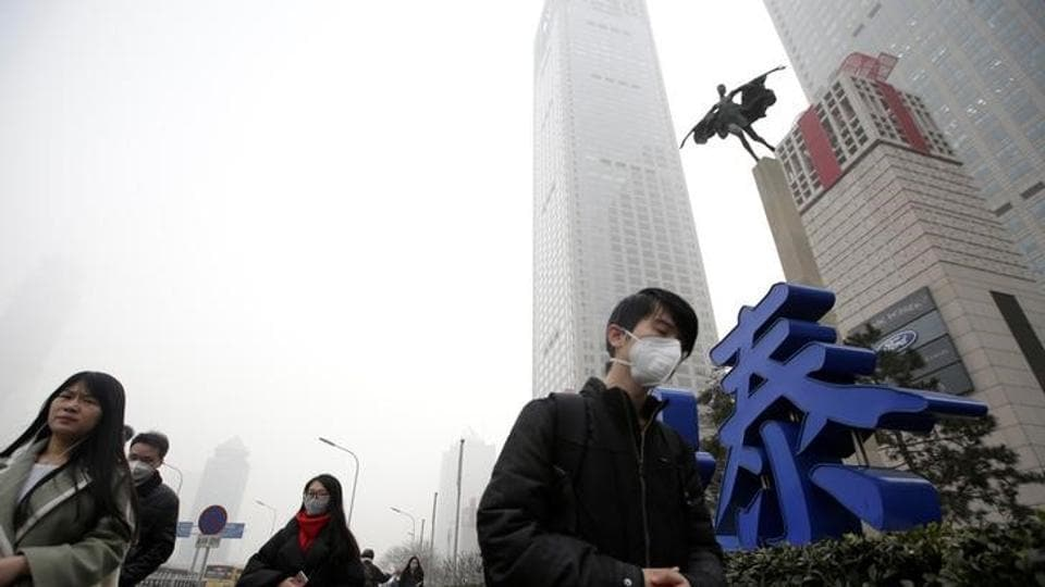 People wearing masks walk past Yintai Centre during the smog after a red alert was issued for heavy air pollution in Beijing's central business district, China.