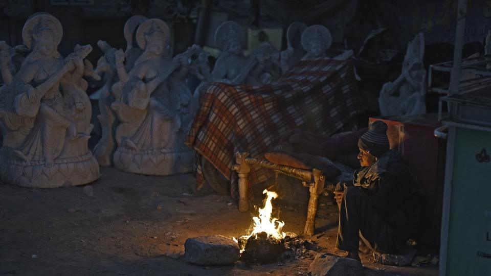 A man guarding idols at an artiste's place warms himself by fire near the Akshardham Temple.  (Ravi Choudhary/HT PHOTO)