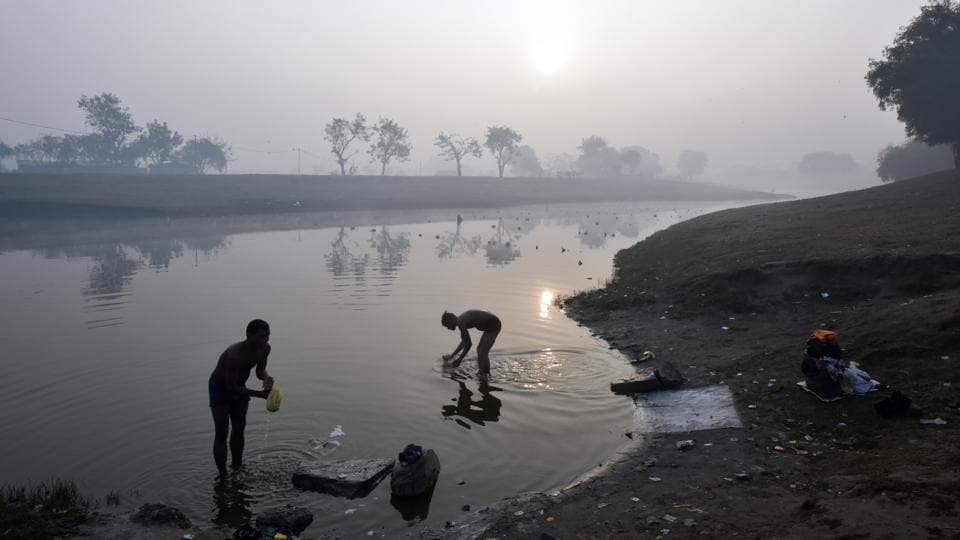 Men wash clothes on the banks of the Yamuna river. (Ravi Choudhary/HT PHOTO)