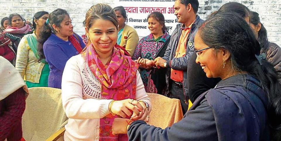 An activist tying a thread on a women's wrist as part of voter awareness campaign in Bulandshahr.