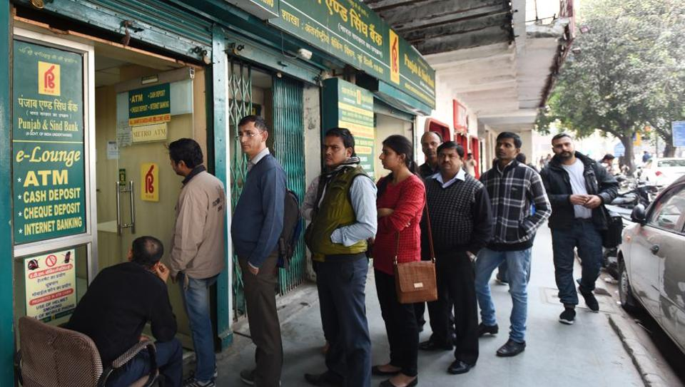 People queue up outside an ATM to withdraw cash near Connaught Place in New Delhi.