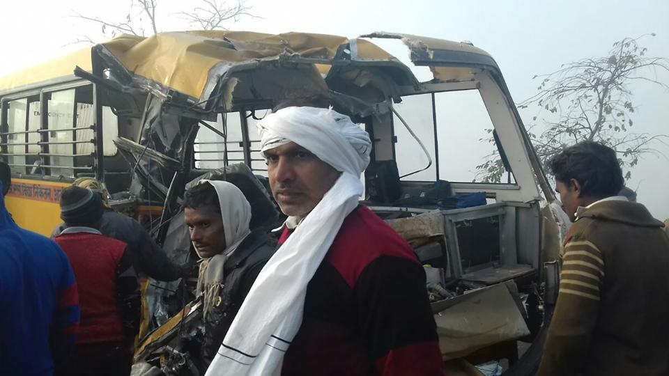 Bystanders gather near the scene of a bus crash in Etah in the state of Uttar Pradesh.