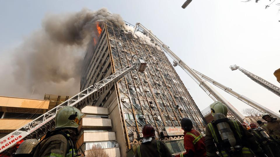 Firefighters battle a blaze that engulfed Iran's oldest high-rise, the 15-storey Plasco building in downtown Tehran. State television said 200 firefighters had been called to the scene and 38 had already been injured battling the blaze before it fell.  (AFP)