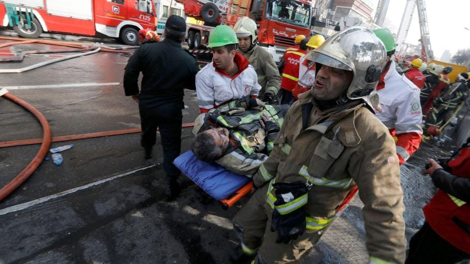 Firefighters carry a wounded comrade as they battle a blaze that engulfed Iran's oldest high-rise building. (AFP)