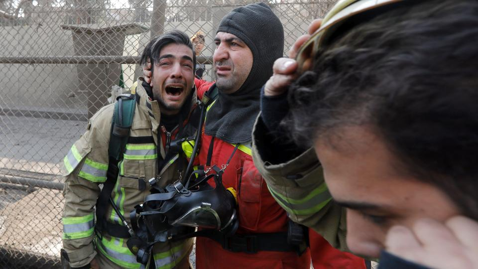 A firefighter consoles his comrade after the collapse of Iran's oldest high-rise. (AFP)