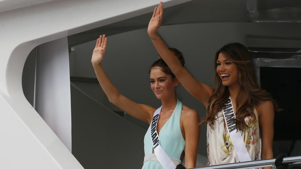 Miss Universe contestants Johanna Acs, left, of Germany, and Keity Drennan of Panama wave from the yacht. (AP)