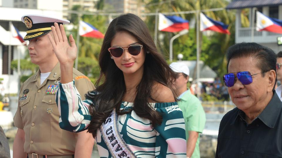 Reigning Miss Universe Pia Wurzbach of the Philippines (C) gestures as she arrives at the navy port. (AFP)