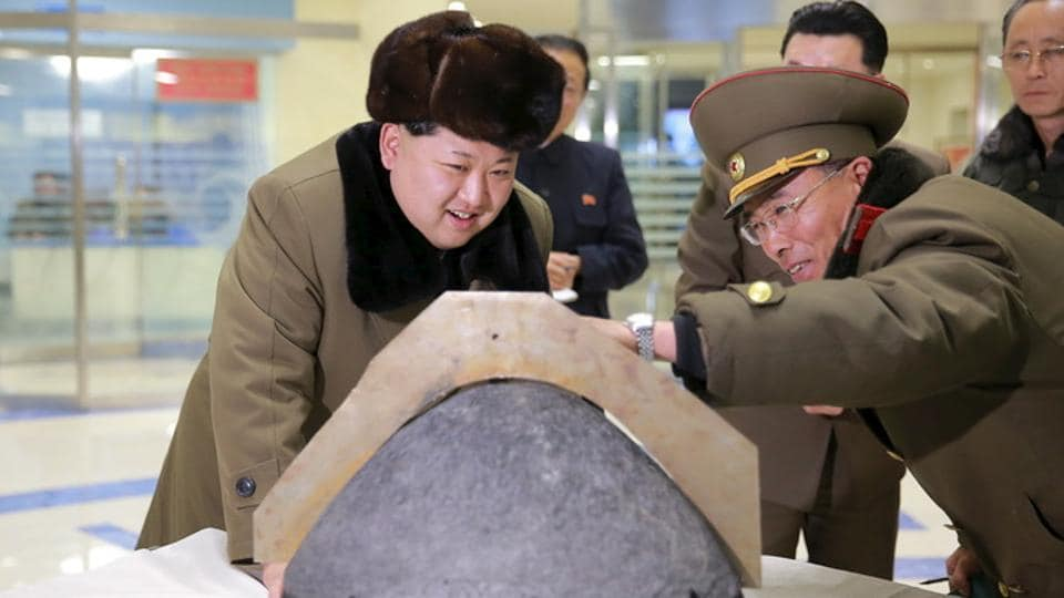North Korean leader Kim Jong Un looks at a rocket warhead tip after a simulated test of atmospheric re-entry of a ballistic missile, at an unidentified location, in this undated photo released by North Korea's Korean Central News Agency (KCNA) .