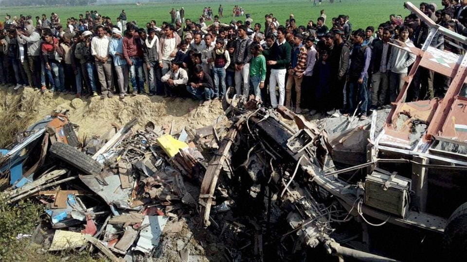 People looking at the mangled remains of vehicles after a school bus collided with a lorry amid dense fog on Aliganj-Paliyali road in Etah district on Thursday.