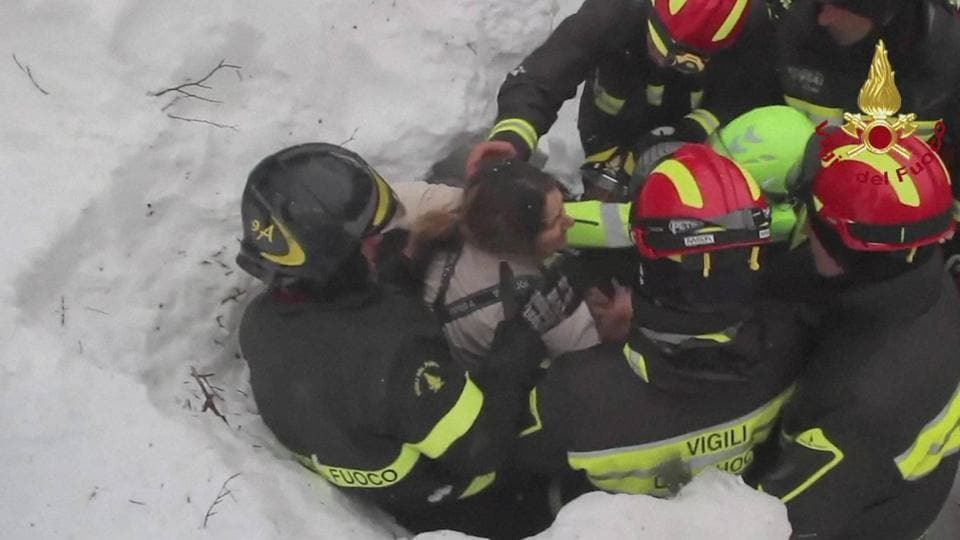 Italian firefighters pull out a woman from the snow and debris of a hotel that was hit by an avalanche on Wednesday, in Rigopiano, central Italy, on January 20, 2017. Eight people were rescued so far from the hotel.