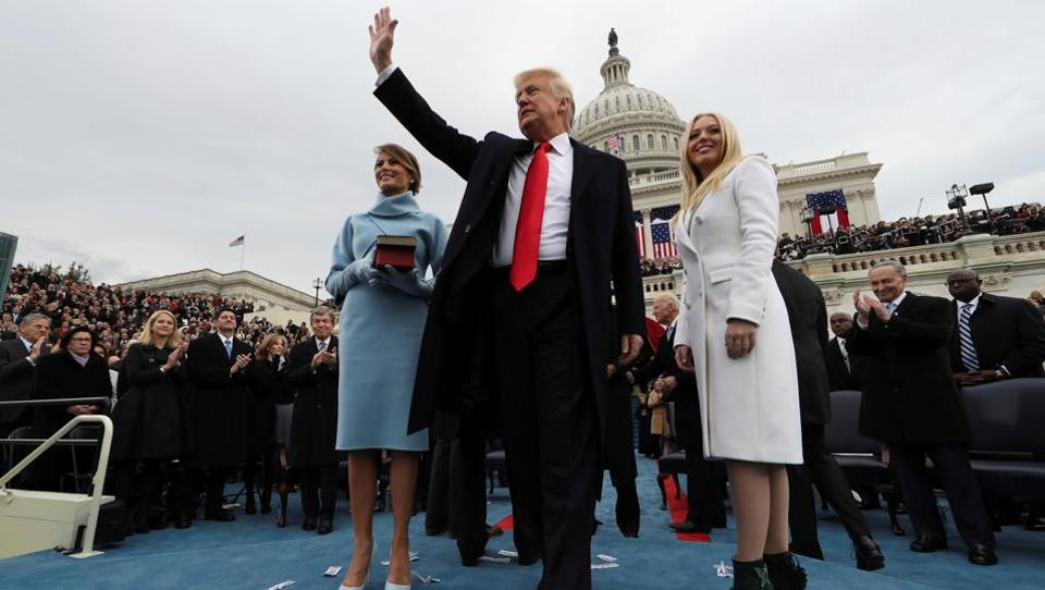 US President Donald Trump acknowledges the audience after taking the oath of office as his wife Melania (L) and daughter Tiffany watch after his during inauguration ceremony on the West front of the US Capitol in Washington, DC. (REUTERS)