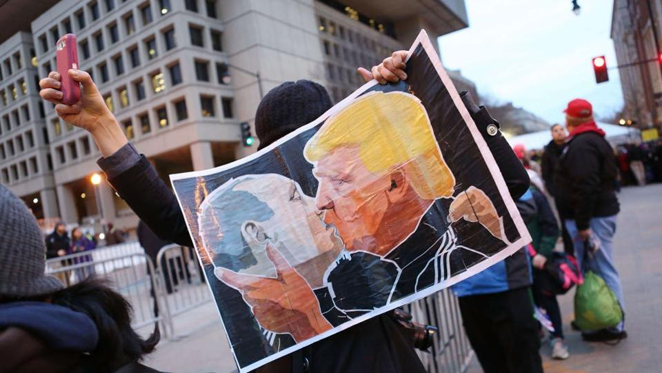 A protester holds a poster depicting President-elect Donald Trump and Russian President Vladimir Putin kissing during an anti-Trump demonstration on January 20, 2017 in Washington, DC. US intelligence services said Russian president Vladimir Putin had launched a campaign that helped Trump and hurt democrat Hillary Clinton in the US presidential elections, (AFP)