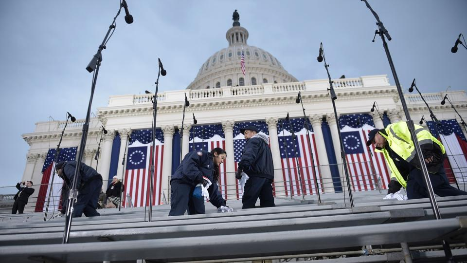 Workers clean up seats on the spectators seats below the Capitol dome in Washington, DC, on January 20, 2017, before the swearing-in ceremony of US President-elect Donald Trump.  (AFP)