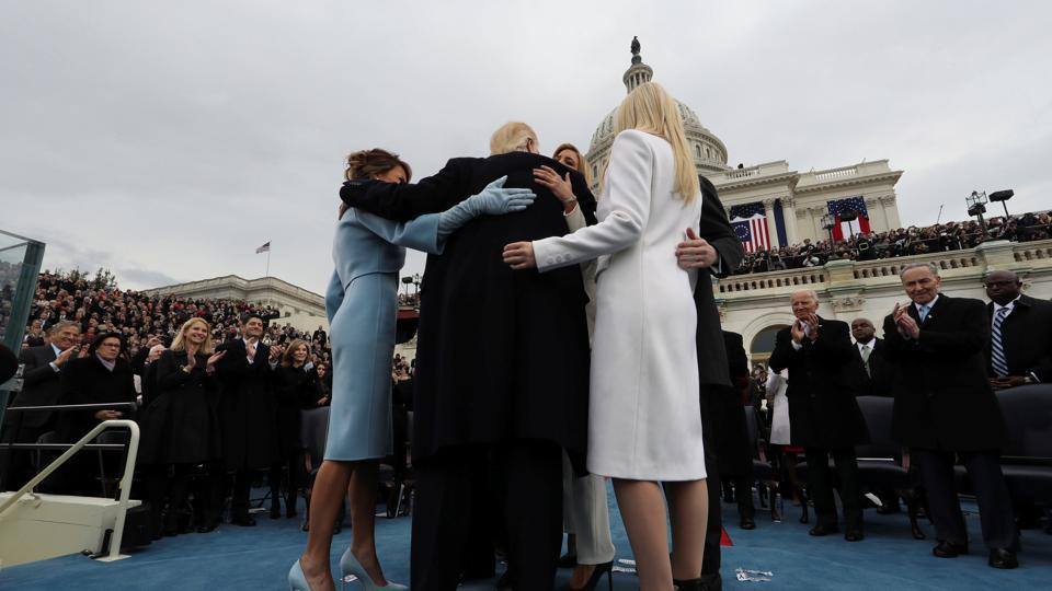 US President Donald Trump embraces his family after taking the oath of office. (REUTERS)
