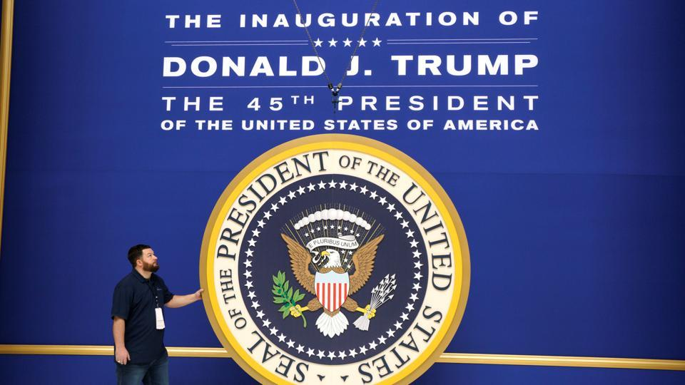 Workers install the presidential seal at the site of the Commander in Chief inaugural ball for President-elect Donald Trump in Washington, DC.